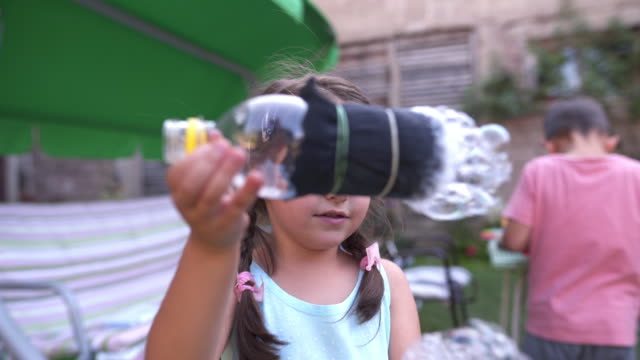 Innocent little girl blowing soap bubbles