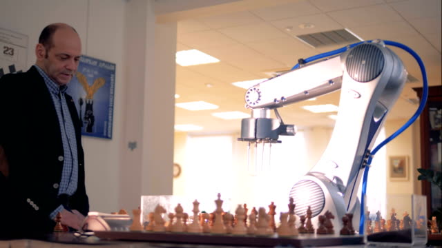 Innovative gaming emulator, robot playing chess with a human. Futuristic robotic concept. video