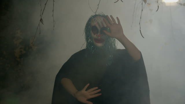 Insane evil halloween clown mime miming a slowly death between walls in darkness and fog video