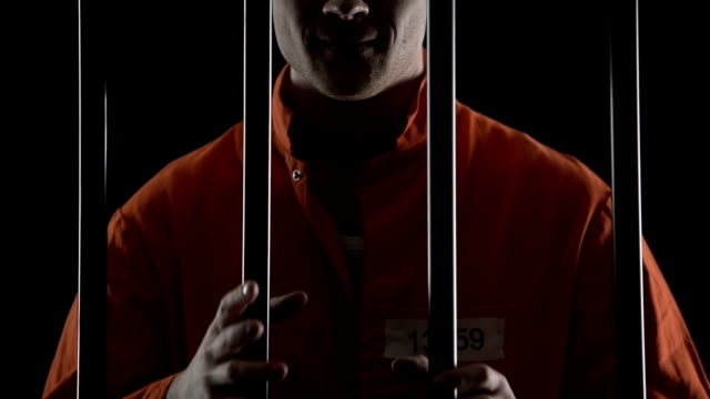 Insane maniac gripping prison cell bars waiting for death penalty, smirking video