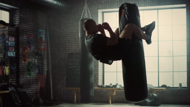 insane punching bag crunches. strong masculine man embrassing the bag with his legs and pumping his abs and core muscles. handsome male trains in a gym with motivational posters. - sacco per il pugilato video stock e b–roll