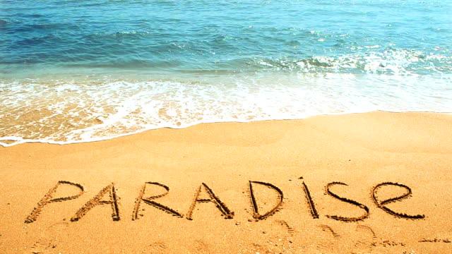 Inscription paradise on sand.