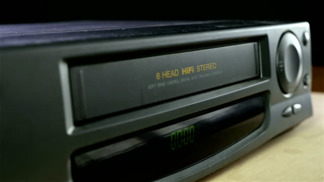 inserting a vhs tape into a vcr player - cassetta video stock e b–roll