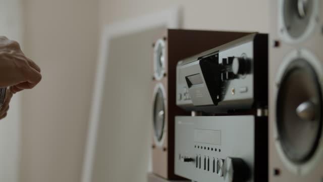 inserimento di casette nel lettore audio - disco audio analogico video stock e b–roll