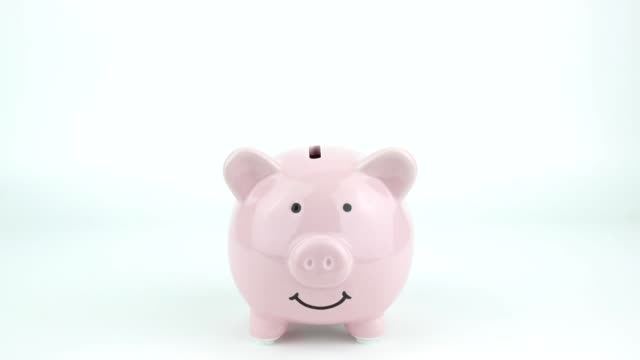 Inserting coins in pink piggy bank Inserting coins in pink piggy bank piggy bank stock videos & royalty-free footage