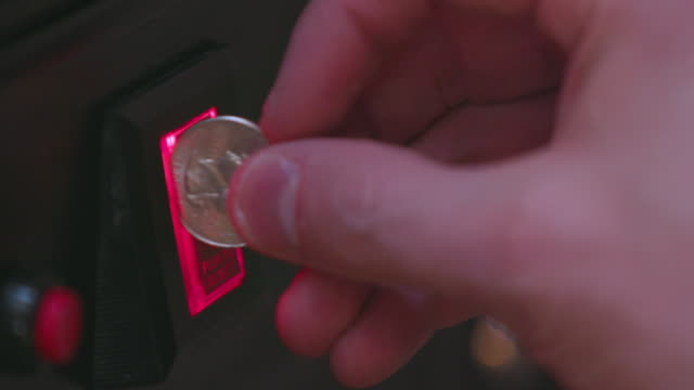 Inserting Quarter Into 25 Cent Arcade Machine Coin Slot
