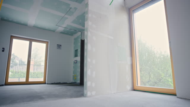 Inside a house with installed plaster walls Wide shot of an inside of a home after the drywall stage. Shot in Slovenia. renovation stock videos & royalty-free footage