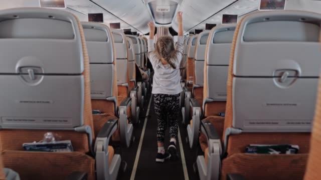 비행기 내부, 비행기 오두막에서 실행 하는 아이, 작은 귀여운 여자 비행기 오두막에 통로 산책 - airplane seat 스톡 비디오 및 b-롤 화면