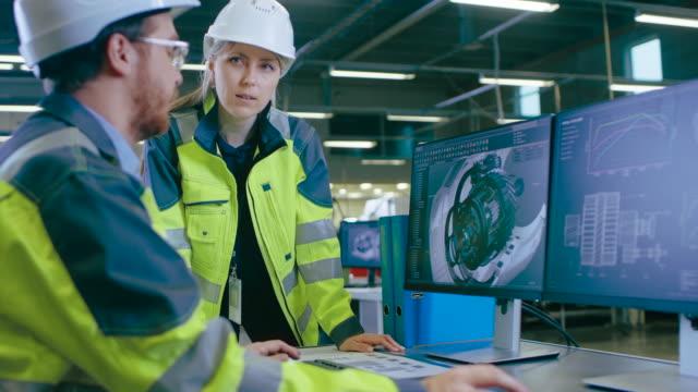 inne i fabriken manliga maskiningenjör och kvinna chief engineer arbete tillsammans på din dator diskuterar de detaljer av 3d-motor modelldesign. - kommunikationssätt bildbanksvideor och videomaterial från bakom kulisserna