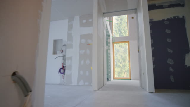 Inside of a home after the drywall stage Wide shot of an interior of a house with finished drywall stage of construction. Shot in Slovenia. renovation stock videos & royalty-free footage