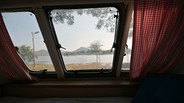 Inside of empty bedroom of motor home and the view through window on lakeside in the morning
