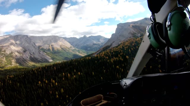 Inside of pilot flying a helicopter on autumn forest in rocky mountains
