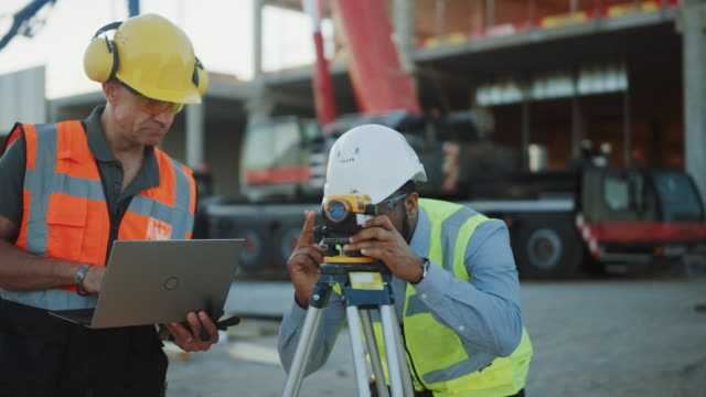 inside of the commercial / industrial building construction site: professional engineer surveyor takes measures with theodolite, using digital tablet computer. in the background skyscraper formwork frames and crane - quality video stock e b–roll