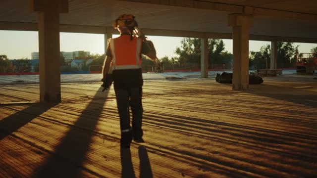 insidan av den kommersiella/industriella byggarbetsplatsen: professionell ingenjör surveyor avslutar dagens jobb bär stativ theodolite och går in i solnedgången. i bakgrunden skyskrapa formwork ramar och kran - byggplats bildbanksvideor och videomaterial från bakom kulisserna