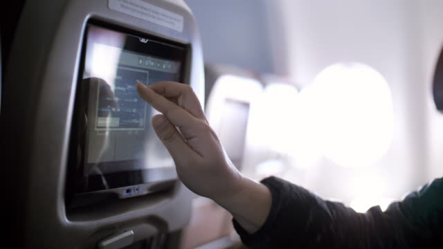 Inside the airplane with Woman passenger using Multimedia touch screen on cabin of airplane , SLOW MOTION