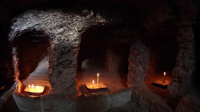 inne i grottan i st tabitha. ljus brinner. bön. - pilgrimsfärd bildbanksvideor och videomaterial från bakom kulisserna