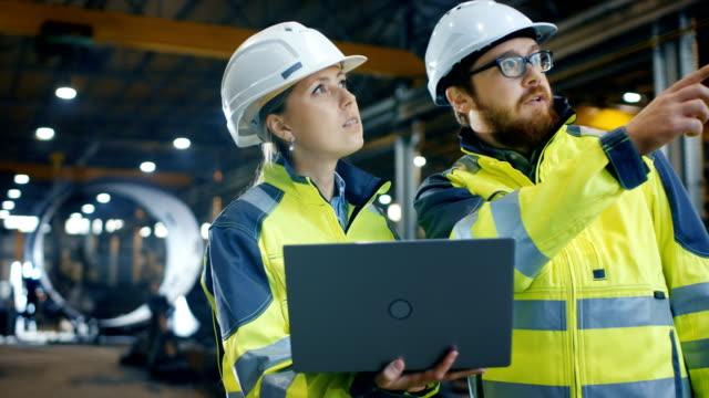 À l'intérieur de la lourde usine industrielle femme ingénieur industriel contient ordinateur portable et a des discussions avec le chef de projet. Dur, ils portent chapeaux et vestes de sécurité. Dans la soudure de fond / ferronnerie en cours. - Vidéo