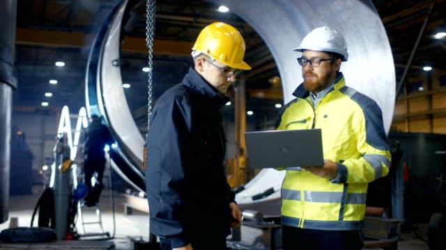 À l'intérieur de la lourde ingénieur industriel usine industrielle contient ordinateur portable et a des discussions avec le chef de projet. Dur, ils portent chapeaux et vestes de sécurité. Dans la soudure de fond / ferronnerie en cours. - Vidéo