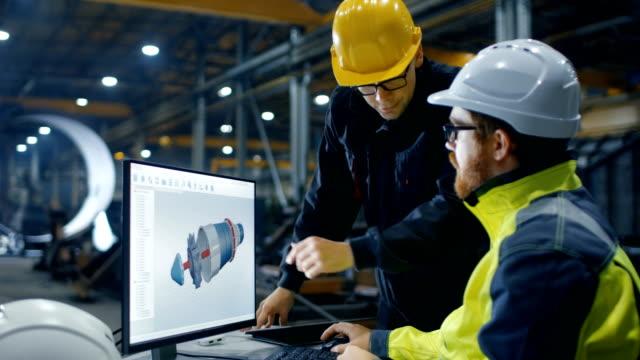 À l'intérieur de l'ingénieur de l'industrie lourde fonctionne sur l'ordinateur personnel, tout en parlant avec le chef de projet. Il conçoit la Turbine / moteur en programme de CAO 3D. - Vidéo
