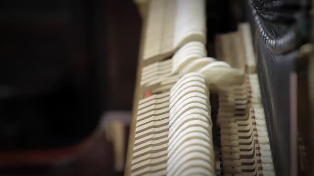 vídeos de stock e filmes b-roll de inside the piano. hammers striking strings. - piano