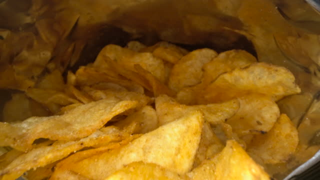 vídeos de stock e filmes b-roll de inside the potato chips bag. opened pack of original taste delicious potato crisps. fast food and unhealthy eating concept - comida salgada