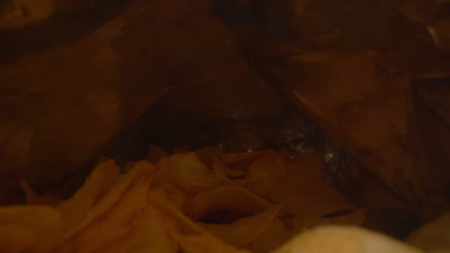 vídeos de stock, filmes e b-roll de dentro do saco de batatas fritas - comida salgada