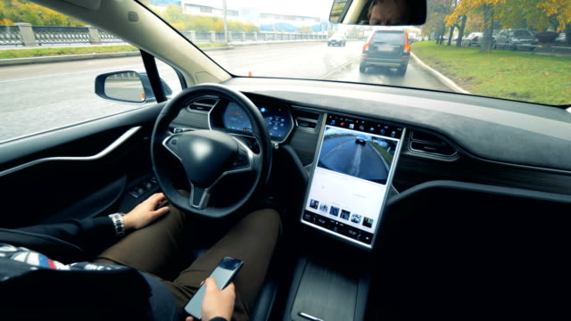 inside view of an automobile which is driving by itself and a man sitting in it - self driving cars stock videos & royalty-free footage