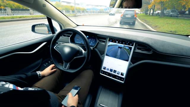 単独で運転している自動車とその中に座っている男の内見 - 自動運転車点の映像素材/bロール
