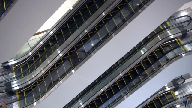 Inside view of empty shopping mall. Escalators moving staircases in motion no people Inside view of empty shopping center. Escalators moving staircases running no people around market retail space stock videos & royalty-free footage