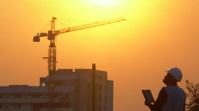 Inspecting Engineer in Construction Site at Sunset video
