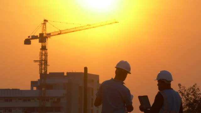 inspecting engineer in construction site at sunset - industria edile video stock e b–roll