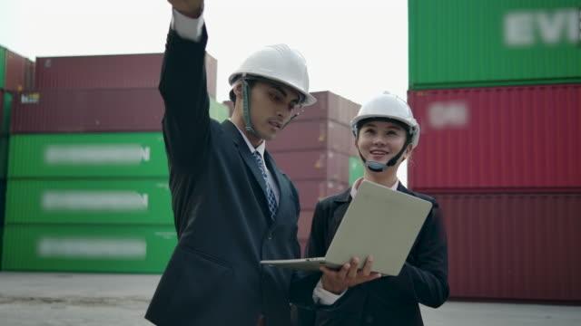 vidéos et rushes de inspections vérifiant l'expédition des conteneurs de fret devant les piles de conteneurs de fret dans la cour de conteneurs d'expédition. - bloc note