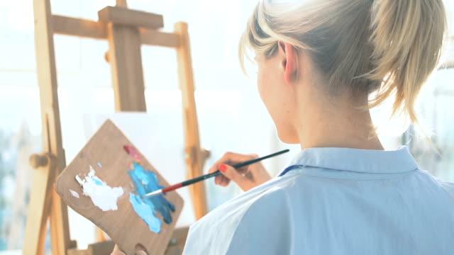 vídeos y material grabado en eventos de stock de estudiante inspirada mezclando colores en paleta de madera, aprendiendo a pintar - espalda humana
