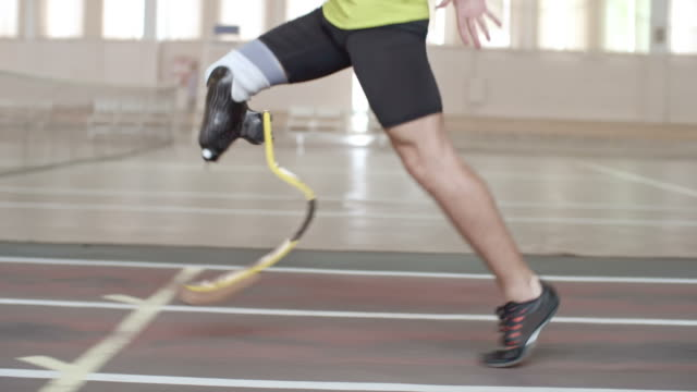 Inspiring Paralympic Athlete Running Tracking shot tilt-up of determinedParalympic athlete with prosthetic leg running on trackin slow motion prosthetic equipment stock videos & royalty-free footage