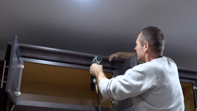 Install of kitchen carpenter installation of crown moulding framing trim in cabinet Install of kitchen carpenter installation of crown moulding framing trim in cabinet cabinet stock videos & royalty-free footage