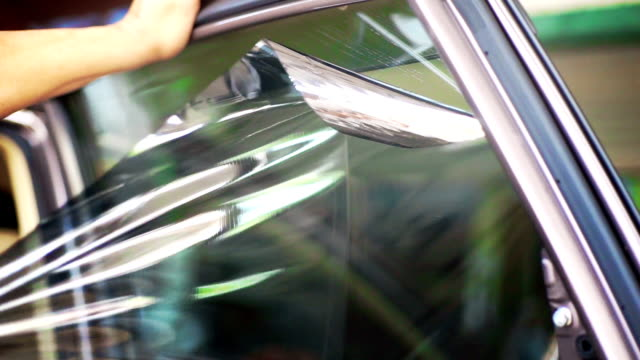 installation of car window tint, hands removing old car window film. - aluminum foil stock videos & royalty-free footage