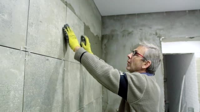 Installation of ceramic tiles in a bathroom. The builder installs the ceramic tile on the wall in the bathroom. tile stock videos & royalty-free footage