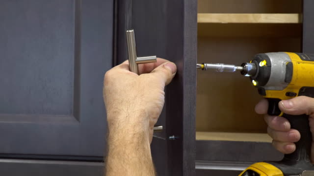 installation of door handles on kitchen white cabinet with a screwdriver installation of door handles on kitchen white cabinet with a screwdriver renovation stock videos & royalty-free footage