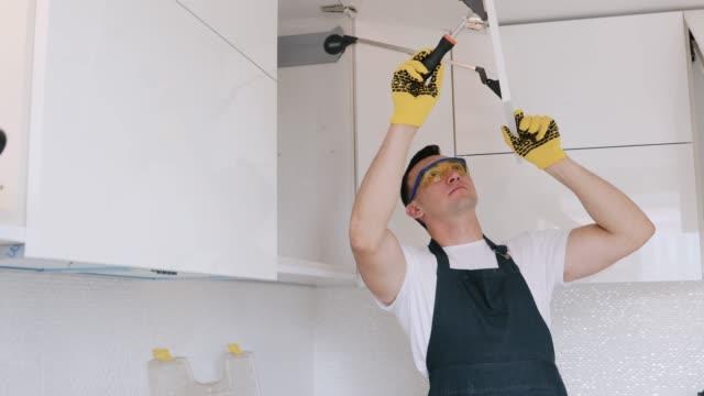 vídeos de stock, filmes e b-roll de instalação de alças móveis em um armário branco. mestre com chave de fenda. - cozinha doméstica