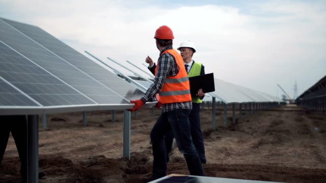 installation of photovoltaic panels on a solar farm - solar panels stock videos & royalty-free footage