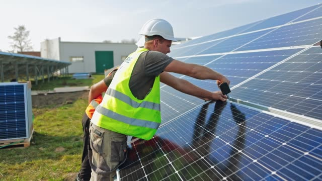 vídeos de stock e filmes b-roll de installation photovoltaic solar panels. worker fixing solar panel to a metal basis with a drill in a sunny day. concept of ecological renewable energy. - solar panel