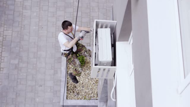 Bидео Installing air conditioners on a building exterior