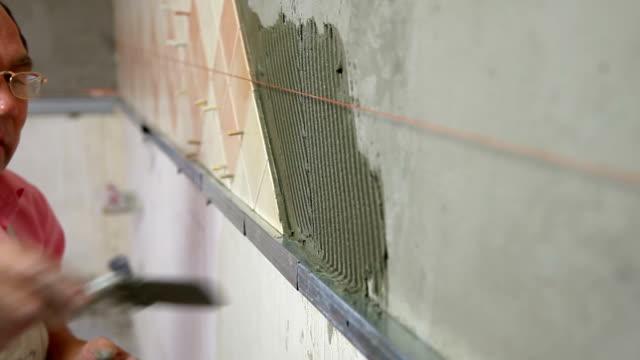 vídeos de stock e filmes b-roll de instalar mosaicos de cerâmica - concrete wall interior