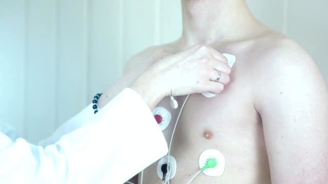 Installing sensors on the patient for heart examination. Monitor HOLTER. This apparatus is monitor heart activity during period Installing sensors on the patient for heart examination. Monitor HOLTER. This apparatus is monitor heart activity during period. electrode stock videos & royalty-free footage
