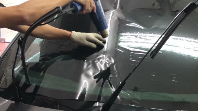 vidéos et rushes de installe un film teinte pour le verre de voiture - image teintée