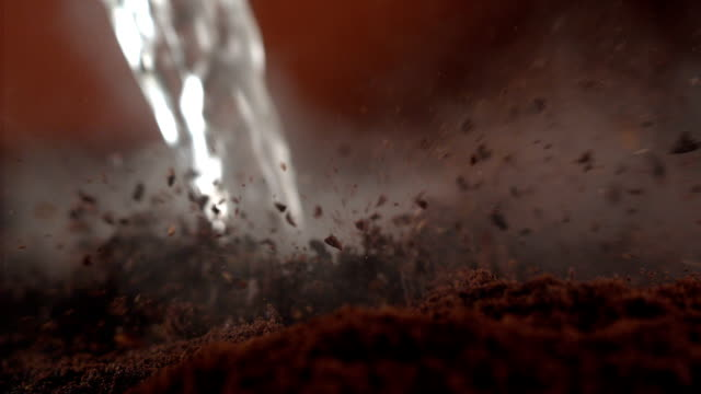 Instant coffee pieces mixing with hot water Instant coffee pieces mixing with water. Super slow motion. Close up. Camera trajectory controled by fast robot arm. Camera Phantom. coffee stock videos & royalty-free footage