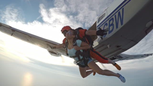 POV Instructor and woman in tandem jumping out of  plane video