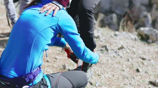 Instructor checking climbing harness before letting her climb group goes sport climbing