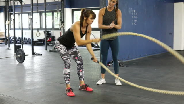 Instructor motivating female exercising with ropes video