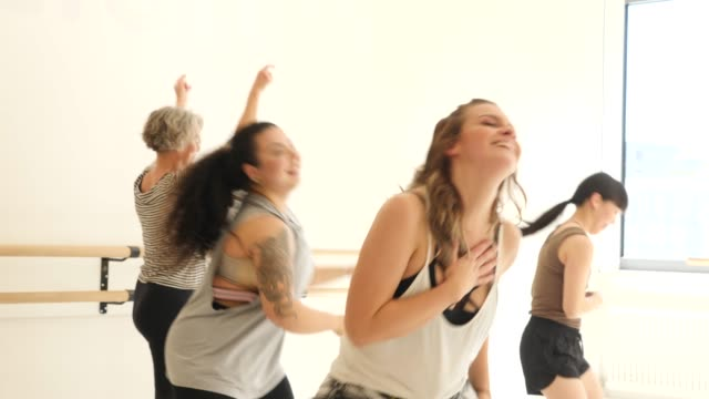 Instructor teaching female students in dance class